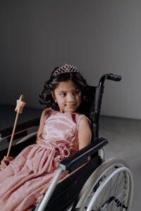 Girl in Pink Dress Sitting on Black Wheelchair